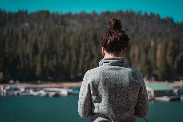 川の前に佇む女性